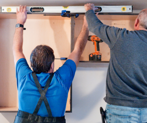 Two men measuring to install new cabinets
